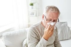 Sick senior man with paper wipe blowing his nose Royalty Free Stock Images