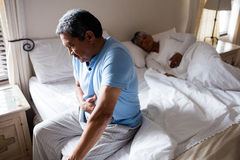 Sick senior man suffering from stomach ache in bedroom. At home Royalty Free Stock Photography