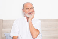 Sick senior sitting on bed with a toothache royalty free stock images