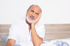 Sick senior sitting on bed with a toothache royalty free stock photo