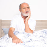 Sick senior sitting on bed with a toothache stock images