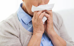 Sick senior woman blowing nose to paper napkin. Health care, flu, hygiene, age and people concept - close up of sick senior woman blowing nose to paper napkin at Stock Photography