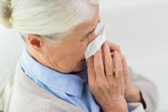 Sick senior woman blowing nose to paper napkin. Health care, flu, hygiene, age and people concept - close up of sick senior woman blowing nose to paper napkin at Stock Photos