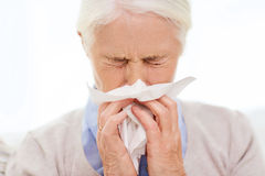 Sick senior woman blowing nose to paper napkin. Health care, flu, hygiene, age and people concept - sick senior woman blowing nose to paper napkin at home Royalty Free Stock Photography