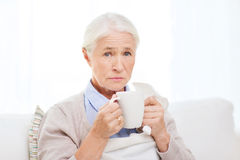 Sick senior woman drinking hot tea at home Royalty Free Stock Photos