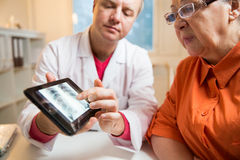 Sick senior woman having a doctor appointment. Male doctor holding digital tablet, showing test results to patient in hospital. X-ray images on screen. Sick Royalty Free Stock Photo