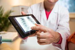 Sick senior woman having a doctor appointment. Male doctor holding digital tablet, showing test results to patient in hospital. X-ray images on screen. Sick Stock Image