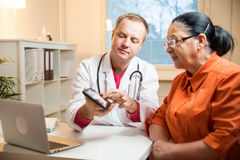 Sick senior woman having a doctor appointment. Male doctor holding digital tablet, showing test results to patient in hospital. X-ray images on screen. Sick Royalty Free Stock Image