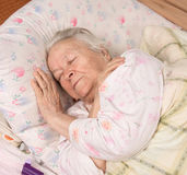 Sick senior woman. Lying at bed Stock Images