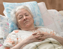 Sick senior woman. Lying at bed Royalty Free Stock Image
