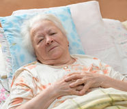 Sick senior woman. Lying at bed Stock Image