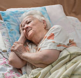 Sick senior woman. Lying at bed Stock Photography