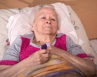 Sick senior woman lying in bed and holding asthma inhaler Royalty Free Stock Images