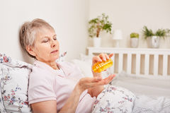 Sick senior woman with medicament Royalty Free Stock Photos