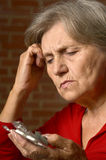 Sick senior woman with pills Stock Images