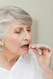 Sick senior woman taking her pills Royalty Free Stock Photos