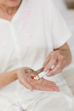 Sick senior woman taking her pills Stock Photography