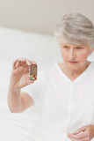 Sick senior woman taking her pills Stock Image