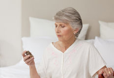 Sick senior woman taking her pills Stock Photo