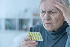 Sick senior woman taking pills. Portrait of sick senior woman taking pills royalty free stock photography