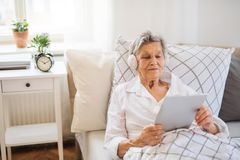 Free Sick Senior Woman With Headphones And Tablet Lying In Bed At Home Or In Hospital. Stock Image - 137837341