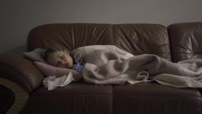 Sick small caucasian girl lying under blanket at home and coughing. The child has fever. Concept of health, illness. Sickness, common cold, treatment stock footage