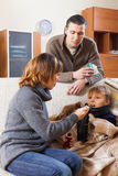 Sick son in home. Loving couple caring for sick son in home Royalty Free Stock Image