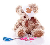 Sick Teddy. With first aid over white background Royalty Free Stock Photo