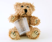 Sick Teddy. Teddy bear holding a medicine cup on a white background Royalty Free Stock Photo