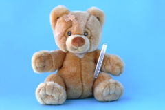 Sick teddy bear. A sick teddy bear with fever thermometer Royalty Free Stock Photography