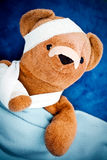 Sick teddy bear. Wrapped in bandages under blanket Royalty Free Stock Photos