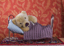 Sick teddy bear in a bed with thermometer Stock Images