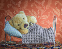 Sick teddy bear lying  with thermometer in bed home Royalty Free Stock Photography