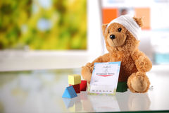 Sick Teddy Bear with Medical Card and Shape Blocks Stock Photo