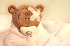Sick teddy bear. With patch in bed Royalty Free Stock Photography