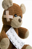 Sick Teddy Bear with pills. Royalty Free Stock Photography