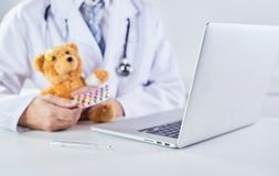 Sick teddy bear receiving medication from doctor. A sick teddy bear receiving prescription medication from a doctor in a paediatric themed concept with laptop stock image