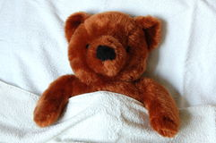 Sick teddy with injury in bed Stock Photo