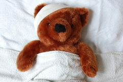 Sick teddy with injury in bed stock images