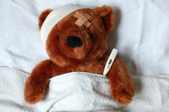 Sick teddy with injury in bed Royalty Free Stock Images