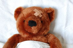 Sick teddy with injury in bed royalty free stock photos