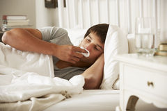 Sick Teenage Boy In Bed At Home Stock Photography