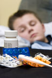 Sick teenage boy and medicines Royalty Free Stock Photo