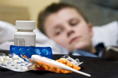 Sick teenage boy and medicines Royalty Free Stock Image