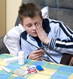 Sick teenage boy and medicines. An ill teenager boy in a sofa, reading pills label, he looks sick and tired Stock Photo