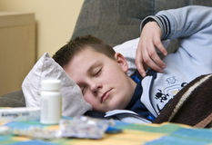 Sick teenage boy and medicines Stock Image
