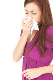 Sick teenage girl with flu blowing nose in tissue Stock Photos