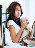 Sick teenage girl with hot tea and medication indoors Royalty Free Stock Images