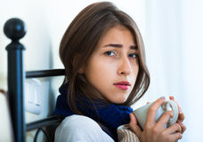 Sick teenage girl with hot tea and medication indoors Stock Images