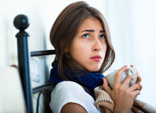 Sick teenage girl with hot tea and medication indoors Stock Photo